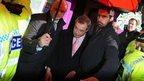 Nigel Farage leaves under police escort after a protest in Rotherham