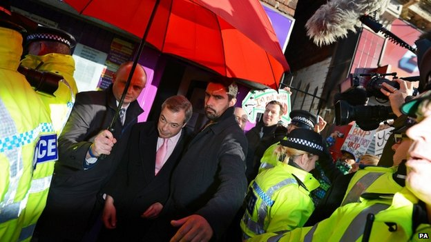 Police escort Nigel Farage out of a venue in Rotherham earlier this month
