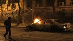 A man walks past a burnt car after minor clashes broke out at the end of an anti-government protest called by leftist groups, in Athens, Greece, on Thursday