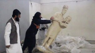 An IS militant appears to push over a statue in Mosul Museum