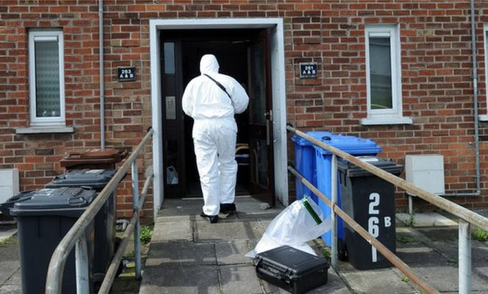 Forensic officer examining George Gray's flat in the aftermath of his murder