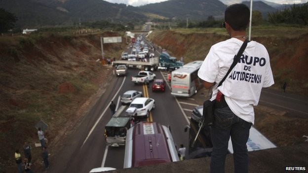 A vigilante stands guard on a bridge during a blockade on a highway near the town of Uruapan in Michoacan state