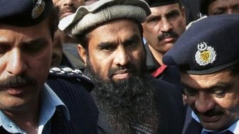 Pakistani police officers escort Zaki-ur-Rahman Lakhvi, center, the main sispect in the Mumbai terror attacks in 2008, after his court appearance in Islamabad, Pakistan, Tuesday, Dec 30, 2014