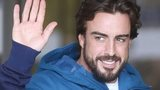 McLaren's Fernando Alonso gestures to the media as he leaves hospital