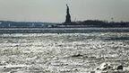 Snow and ice floats in the Hudson river with the Statue of Liberty in the background