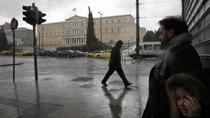 People shelter from the rain in Athens, 27 February