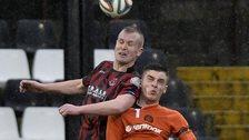 Crusaders striker Jordan Owens fights out an aerial duel with Carrick's Ryan Arthur
