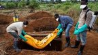 Volunteers bury an Ebola victim in Waterloo, southeast of Freetown - 7 October 2014