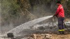 Man training water hose on burning ground in Patagonia National Park