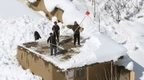 Afghans clean snow from their roofs after the avalanche in the Paryan district of Panjshir province (27 February 2015)