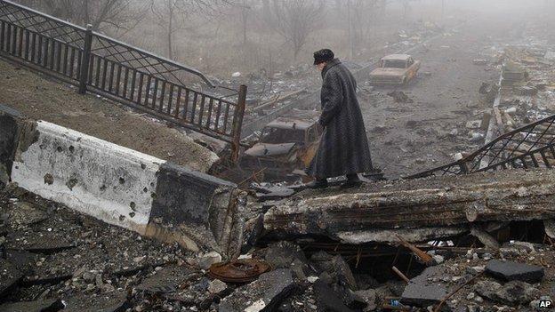 An elderly woman walks across a destroyed bridge near the airport in Donetsk, Ukraine - 1 March 2015