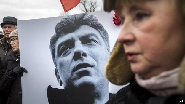 People carry a placard with the image of opposition leader Boris Nemtsov during a march in St Petersburg  on 1 March 2015.
