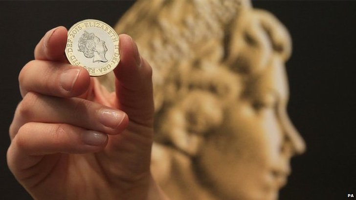 A new two-pound coin in front of the Arnold Machin coinage portrait of Queen Elizabeth II during an unveiling ceremony for the latest coinage portrait of Queen Elizabeth II at the National Portrait Gallery in London