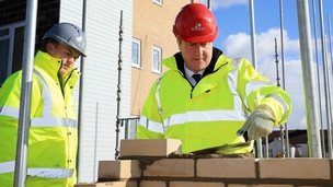 David Cameron lays bricks with apprentice brick layer Josh Adams during a visit to a new housing development in Grays, Essex