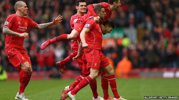 Jordan Henderson (C) of Liverpool celebrates with teammates after scoring the opening goal during the Barclays Premier League match between Liverpool and Manchester City at Anfield