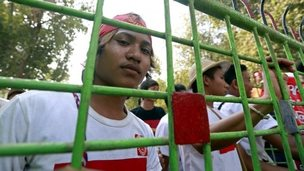 A student looks from behind a gate at the protest camp in Letpadan, Bago division, Myanmar, 02 March 2015.