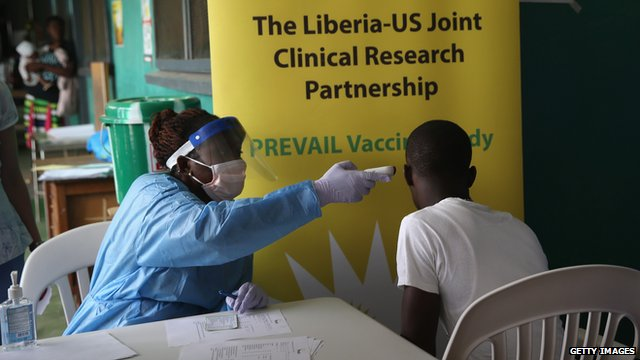 A nurse takes the temperature of a volunteer in the Ebola vaccine trials on 2 February, 2015 in Monrovia, Liberia