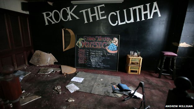 The stage - rock the Clutha backdrop, dusty leaflets, a music stand, a list of future gigs
