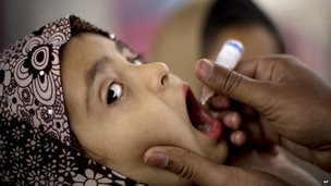 A Pakistani health worker gives polio vaccine to a child at a bus terminal in Rawalpindi, Pakistan. 16 February 2015