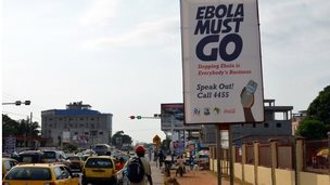 """A picture taken on February 23, 2015 shows an Ebola campaign banner with the new slogan """"Ebola Must GO"""" in Liberia"""