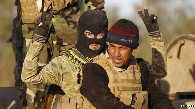 Shia militiaman makes victory gestures in Salahuddin province, Iraq (2 March 2015)