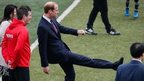 Prince William kicks a football in China