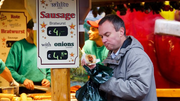 A man buys a bratwurst at the Christmas market
