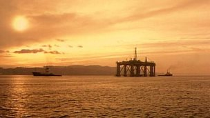 An oil rig and boat at sunset
