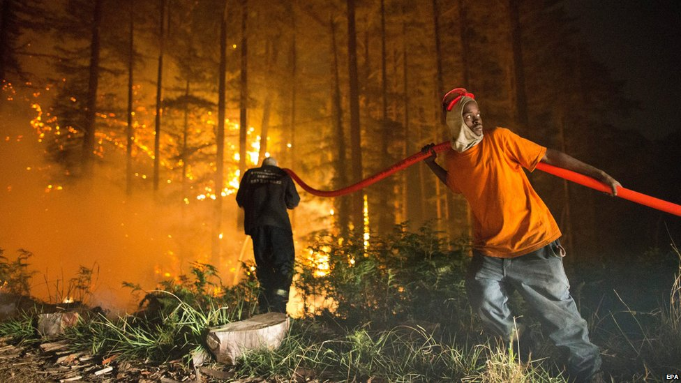 Firefighters tackle a blaze raging in the Tokai forest in Cape Town, South Africa
