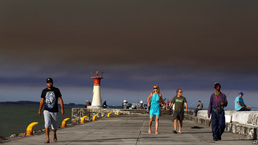 South Africans walk on Kalk Bay harbour wall below a cloud of smoke from an indigenous Fynbos vegetation fire in Cape Town, South Africa.