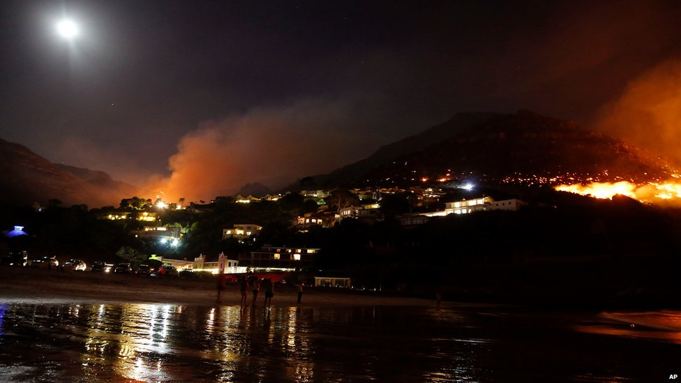 People watch fires at Houtbay on the outskirts of the city of Cape Town, South Africa, Tuesday, March 3, 2015.