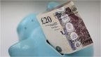 A £20 note placed in top of a piggy bank