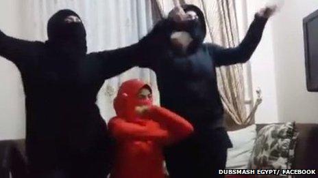 Women dressed as militants bellydancing