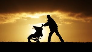 A man pushing a buggy, seen in silhouette at sunset