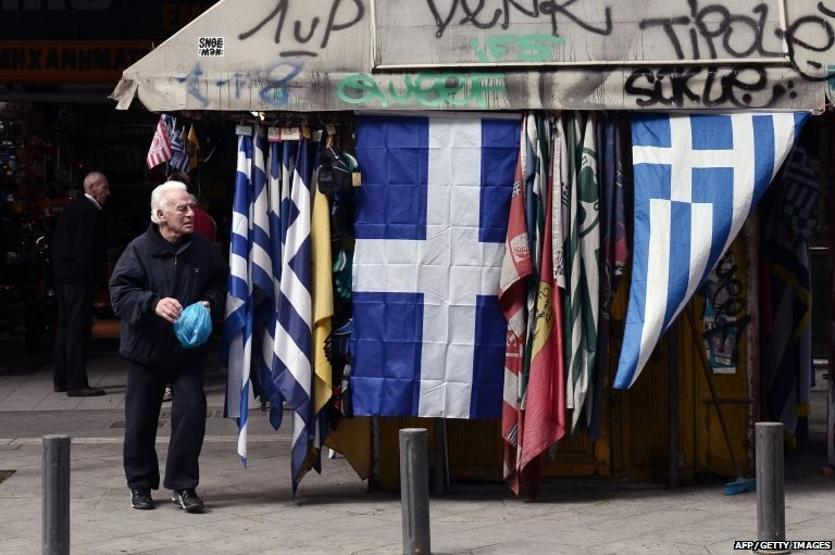 A man walks by greek flags for sale