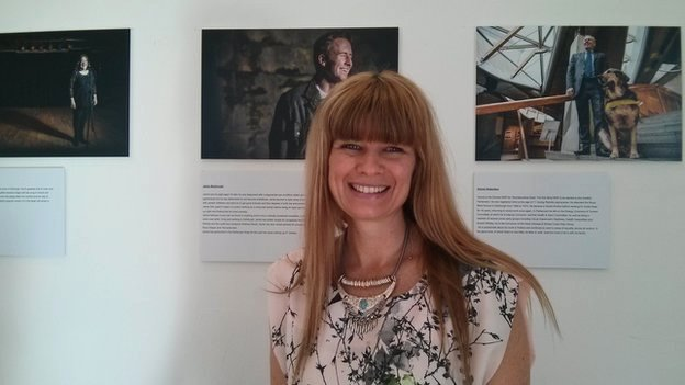 Photographer Trudy Stade stands in front of her portrait of Jamie MacDonald, who inspired her project