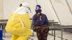 A health worker wearing protective gear tends to a newly-admitted suspected Ebola patient in a quarantine zone at a Red Cross facility in Sierra Leone (December 2014)