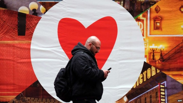 A man texts on his smartphone as he walks