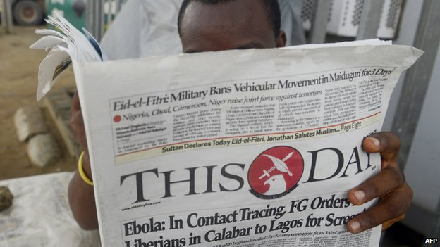 A man reading a ThisDay newspaper in July 2014