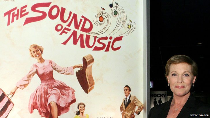 Dame Julie Andrews beside a Sound of Music poster