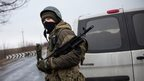 A pro-Russian separatist stands guard at a checkpoint on the road heading to Mariupol on 4 March 2015 in  Ukraine