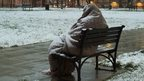 A homeless person wrapped in a blanket on a bench in the snow