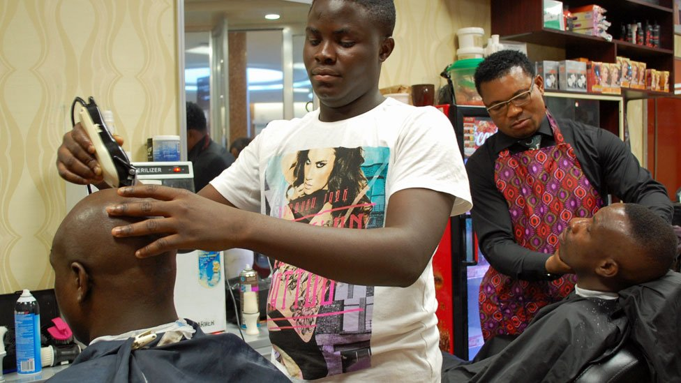 Barbers at work at Bruno's Place hair salon in Ikeja Mall in Lagos, Nigeria