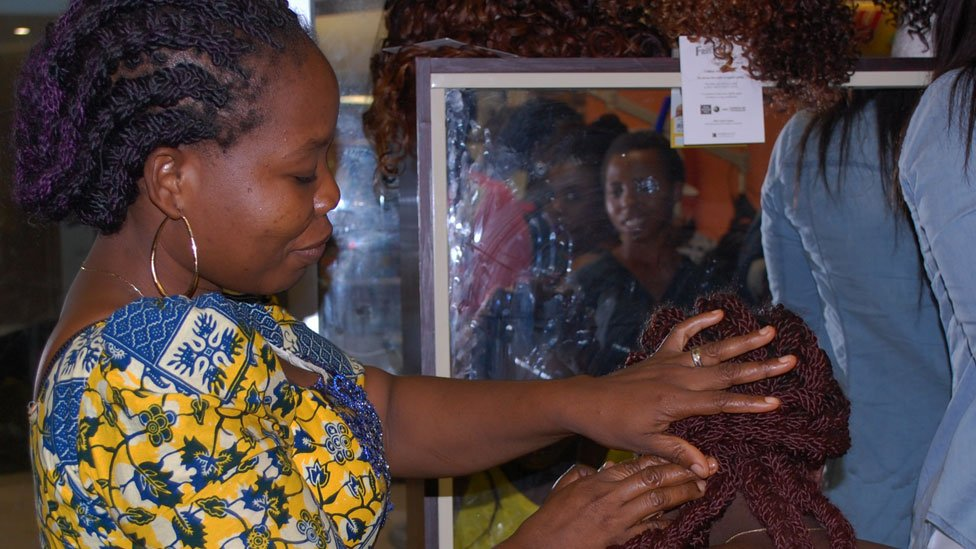 A hairdresser fixing braids at Bruno's Place hair salon in Ikeja Mall in Lagos, Nigeria