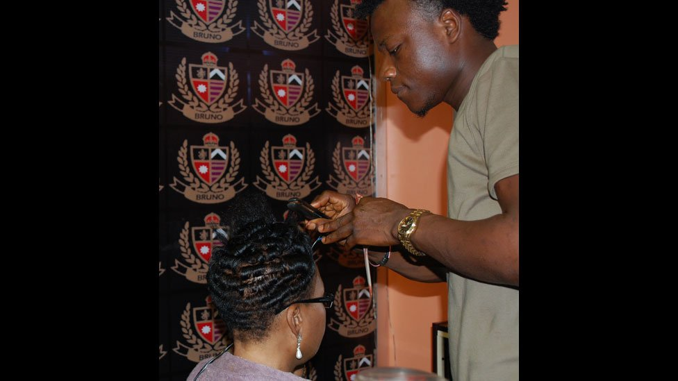 A hairdresser curling hair at Bruno's Place hair salon in Ikeja Mall in Lagos, Nigeria