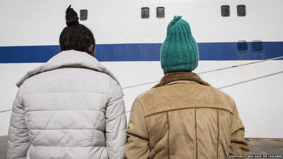 Eritrean sisters, Feben (green hat) + Lem-Lem (White coat) wait on the docks of Lampedusa