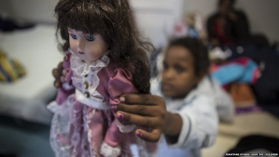 A young migrant girl clutches a toy doll