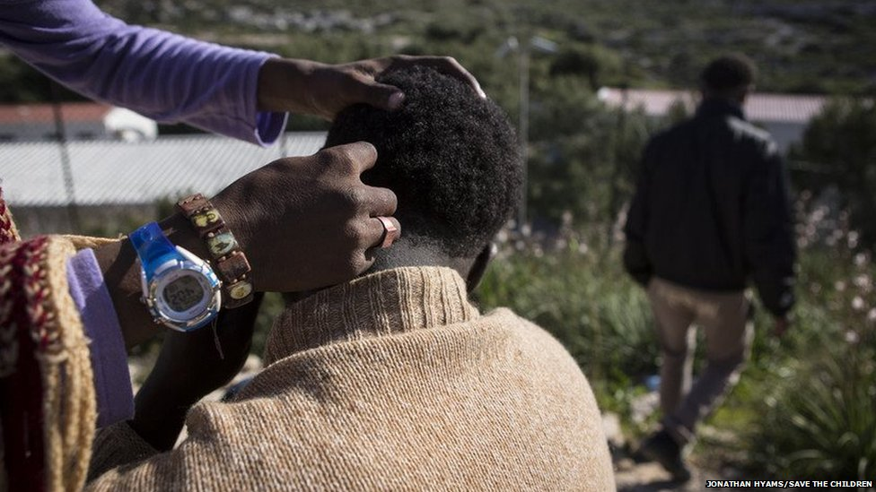 A migrant cuts another's hair with a razorblade