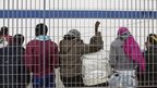 Child migrants wait at the docks on Italy's Lampedusa island