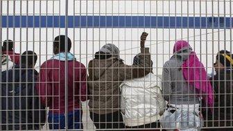 Child migrants wait at the docks on Italy's Lampedusa island
